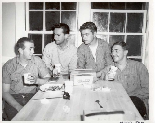 """The original caption stated: """"Rescuers discuss the rescue. Left to right are Coast Guardsmen Bernard Webber, who piloted the rescue boat; Engineman second class Andrew Fitzgerald, Seaman Richard Livesey and Seaman Irving Maske. Photo by Richard Kelsey, Chatham."""" Photo credit: Cape Cod Community College."""